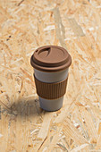 Paper cup of takeaway coffee with brown silicone ring