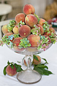 Glass bowl with peaches and green hydrangea blossoms