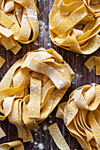 Nests of uncooked tagliatelle on wooden background