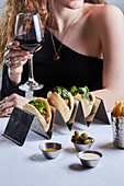 A model in a restaurant with red wine and chicken shawarma in pita, pickles, Amba, tahini and french fries