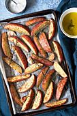 Seasoned potato wedges on a baking tray.