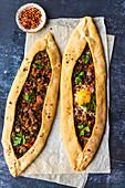 Türkische Pide, gefüllt mit Rindfleisch und Ei
