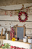 Herbst-Arrangement mit roten Zwiebeln, Schiefertafel, Besteck und Bechern