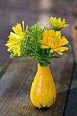 Kleiner Strauß aus Ringelblumen und Fenchelblüten in Zierkürbis als Vase