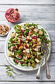 Pear, salad with gorgonzola cheese, pomagranate seeds, rocket, walnuts, walnuts and half of pomegranate