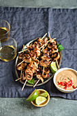 Thai chicken satay skewers on a silver tray served with peanut sauce and fresh lime