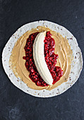 A fruit and peanut butter wrap with bananas and raspberries