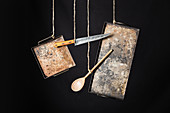 Rustic metal baking sheets, knife and wooden spoon hanging on ropes