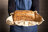 Freshly baked bread loaf with seeds on parchment