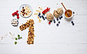 Ingredients for healthy breakfast and muesli laid out to form a '1'