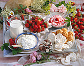 Still life with strawberries, strawberry curd, cream puffs, meringue, chocolates, whipped cream and milk