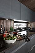 Dark fitted kitchen, food preparation on worktop
