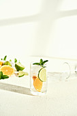 Glass of water with lime, orange and mint