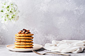 Stack of pancakes with honey and almonds