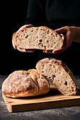 Frisch gebackenes Brot, Hände halten eine Hälfte