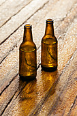 Two beer bottles on wooden surface