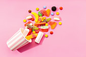 Multicolored jelly candies and marshmallows scattered on pink background