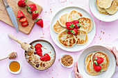 Pancakes and bowl of yoghurt and granola with strawberries