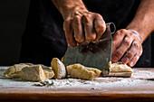 Man dividing raw bread dough with scraper