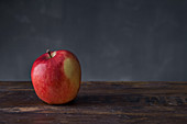 Whole red apple on wooden surface