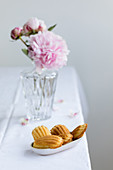 Madeleines in a small bowl in front of a vase with peonies