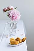 Madeleines im Schälchen vor Vase mit Pfingstrosen