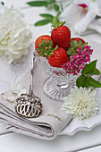 Still life with strawberries in glass bowls, flowers and silver pastry tongs