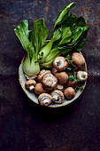 Pak choi and brown mushrooms in a ceramic bowl