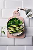 Green mini asparagus and fresh spinach in a ceramic bowl