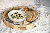 Porridge mit Früchten auf Frühstückstablett im Bett