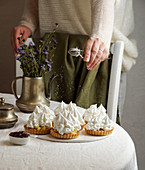 Decorating tartlets with cream and meringue icing