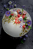 Yoghurt cake with tonka bean, strawberries and flower decoration
