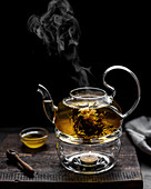 Blossom tea in a glass teapot on a warmer against a black background
