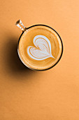 A glass cup of cappuccino with latte art in shape of heart