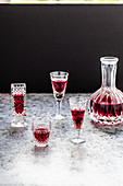 Raspberry liqueur in glasses and a carafe against a black background