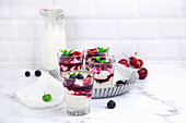 Small glasses with mascarpone cream and egg-free cream with cherries and blackberrie