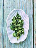 Dried mint leaves on a leaf-shaped porcelain plate