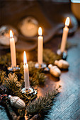 Christmas table decorations with sprigs of pine and lit candles