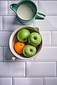 Apples and oranges in ceramic bowl with milk jug
