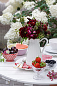 Bouquet of red summer flowers and Love-in-a-Mist seed pods and bowls with strawberries, cherries, and blackberries