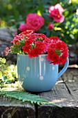 Rote Verbenenblüten in blauer Tasse