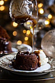 A holiday table set up with sticky toffee pudding with pecan caramel sauce being drizzled on top