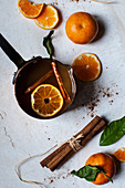 Apple cider heated in a copper pot, with oranges with leaves, orange slices, and cinnamon sticks