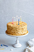 Honey cake with burning candles for birthday