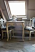 Sitzplatz mit Tisch und Stühlen im Shabby Chic unterm Dachfenster