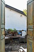 Blick durch Doppeltüren mit Patina auf die Dachterrasse im Vintagestil