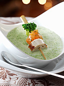 Cream of broccoli soup with salmon and sausage on a skewer