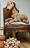 Antikes Stofftier auf altem Stuhl und getrockneter Rosenstrauß
