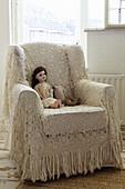 Puppe auf einem Sessel mit gehäkeltem Tuch als Überwurf