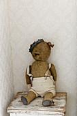 Alter, abgenutzter Teddy mit Krone als nostalgische Deko
